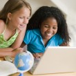 Two Young Girls Doing Their Homework On A Laptop - Stock Photo