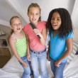 Three Young Girls Standing On A Bed, Singing Into A Hairbrush - Stock Photo