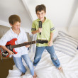 Two Boys Standing On A Bed, Playing Guitar And Singing Into A Ha - Stock Photo