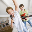 Two Boys Standing On A Bed, Playing Guitar And Singing Into A Ha — Stock Photo #4780336