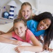 Three Young Friends Lying On Top Of Each Other - Stock Photo