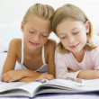 Two Young Girls In Their Pajamas, Reading A Book — Stock Photo