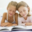 Two Young Girls In Their Pajamas, Reading Book — Stock Photo #4780387