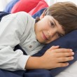 Foto Stock: Young Boy Lying Down In His Bed
