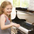 Stock Photo: Young Girl Playing Piano