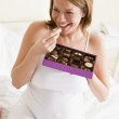 Pregnant woman in bed eating chocolate smiling — Stock Photo #4780513