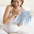 Pregnant woman packing baby clothing in suitcase smiling — Stock Photo #4780540