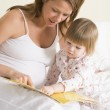 Pregnant woman in bedroom reading book with daughter — Stock Photo #4780548