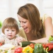 Mother and daughter in kitchen making a salad smiling — Stock Photo