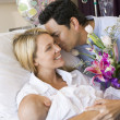 New mother with baby and husband in hospital smiling — Stock Photo