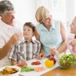 Foto Stock: Grandparents And Grandchildren Prepare A meal,mealtime Together