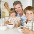 Father With Children As They Eat Breakfast And Mother In The Bac - Stock Photo