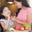 Mother Offering Daughter A Piece Of Freshly Chopped Pepper - Stock Photo