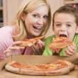 Foto de Stock  : Mother And Son Eating PizzTogether
