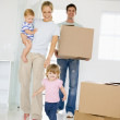 Family with box moving into new home smiling — Stock Photo