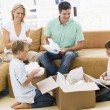 Family unpacking boxes in new home smiling — Stock Photo #4781248