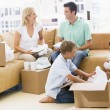 Family unpacking boxes in new home smiling — Stock Photo #4781250