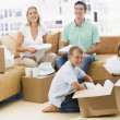 Family unpacking boxes in new home smiling — Stock Photo #4781252