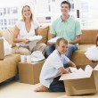 Stock Photo: Family unpacking boxes in new home smiling