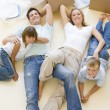 Family lying on floor by open boxes in new home smiling — Stock Photo