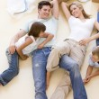 Family lying on floor by open boxes in new home smiling — Stock Photo #4781257
