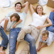 Royalty-Free Stock Photo: Family lying on floor by open boxes in new home smiling