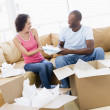 Couple unpacking boxes in new home smiling — Stock Photo