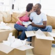Couple unpacking boxes in new home kissing and smiling — Foto Stock