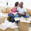 Couple unpacking boxes in new home kissing and smiling — Lizenzfreies Foto