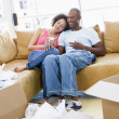 Couple relaxing with coffee by boxes in new home smiling — Foto Stock