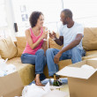 Couple toasting champagne by boxes in new home smiling — Foto Stock