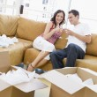 Couple relaxing with champagne by boxes in new home smiling — Stock Photo