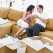 Couple relaxing with champagne by boxes in new home smiling — Foto Stock
