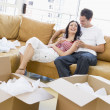 Couple relaxing with champagne by boxes in new home smiling — Lizenzfreies Foto