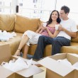 Couple relaxing with coffee by boxes in new home smiling — Lizenzfreies Foto