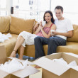 Couple relaxing with coffee by boxes in new home smiling — Stock Photo #4781316