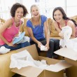 Three girl friends unpacking boxes in new home smiling — Stock Photo