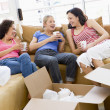 Royalty-Free Stock Photo: Three girl friends relaxing with coffee by boxes in new home smi