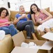 Three girl friends relaxing with coffee by boxes in new home smi - ストック写真