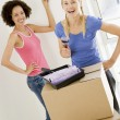 Two women with paint swatches in new home smiling — Stock Photo