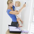 Mother holding son while painting room in new home smiling — Stock Photo #4781360