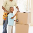 Father wearing tool belt standing by son and boxes in new home s — Stock Photo #4781382