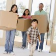 Family with boxes moving into new home smiling — Stock Photo #4781390
