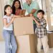 Family with boxes in new home smiling — Foto de Stock