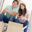 Royalty-Free Stock Photo: Couple sitting on staircase with boxes in new home smiling