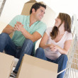 Couple sitting on staircase with boxes in new home smiling — Foto de Stock