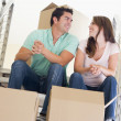 Couple sitting on staircase with boxes in new home smiling - ストック写真
