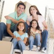 Family sitting on staircase with boxes in new home smiling — Stock Photo #4781401