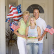 Family at front door on fourth of July with flags and cookies sm — Zdjęcie stockowe