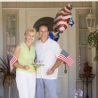 Couple at front door on fourth of July with flags and cookies sm - Stockfoto